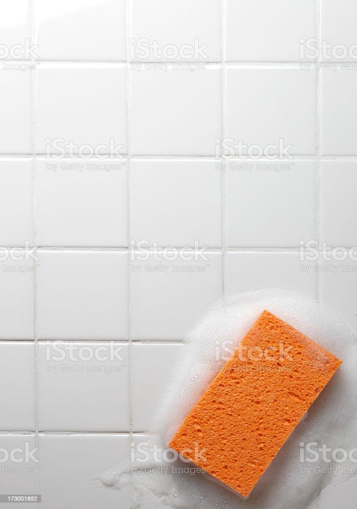 Orange soapy sponge on white bathroom tiles stock photo