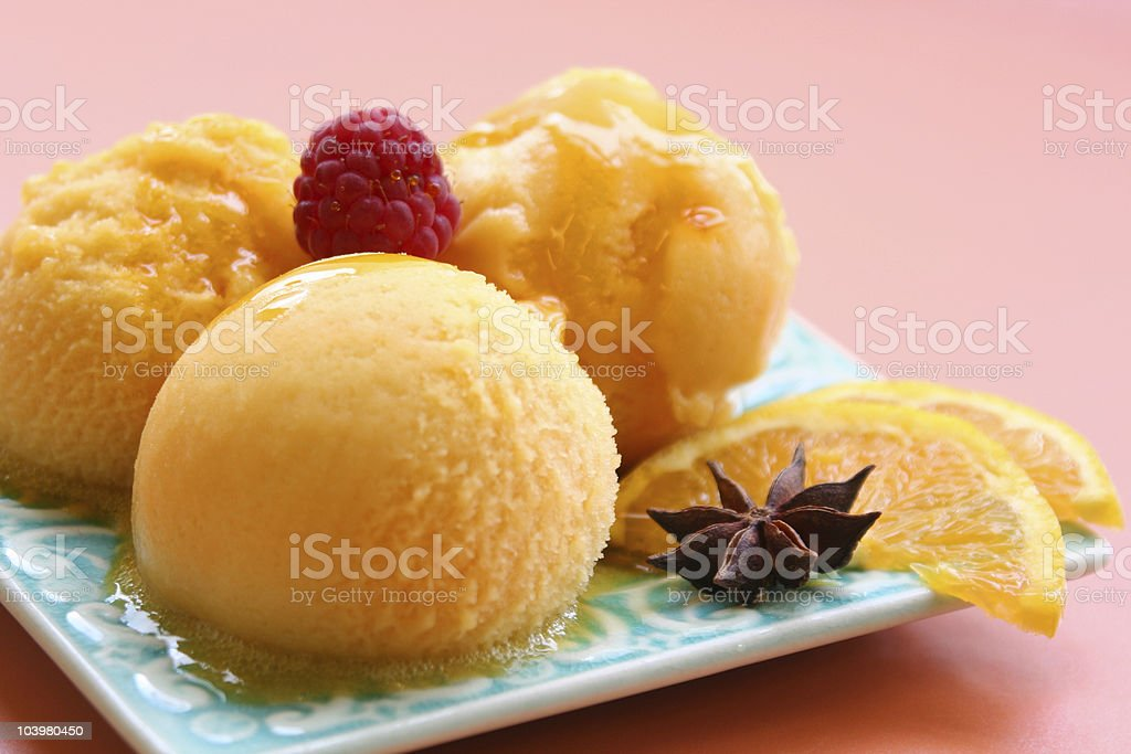 Orange sorbet served on a plate with slices of orange stock photo