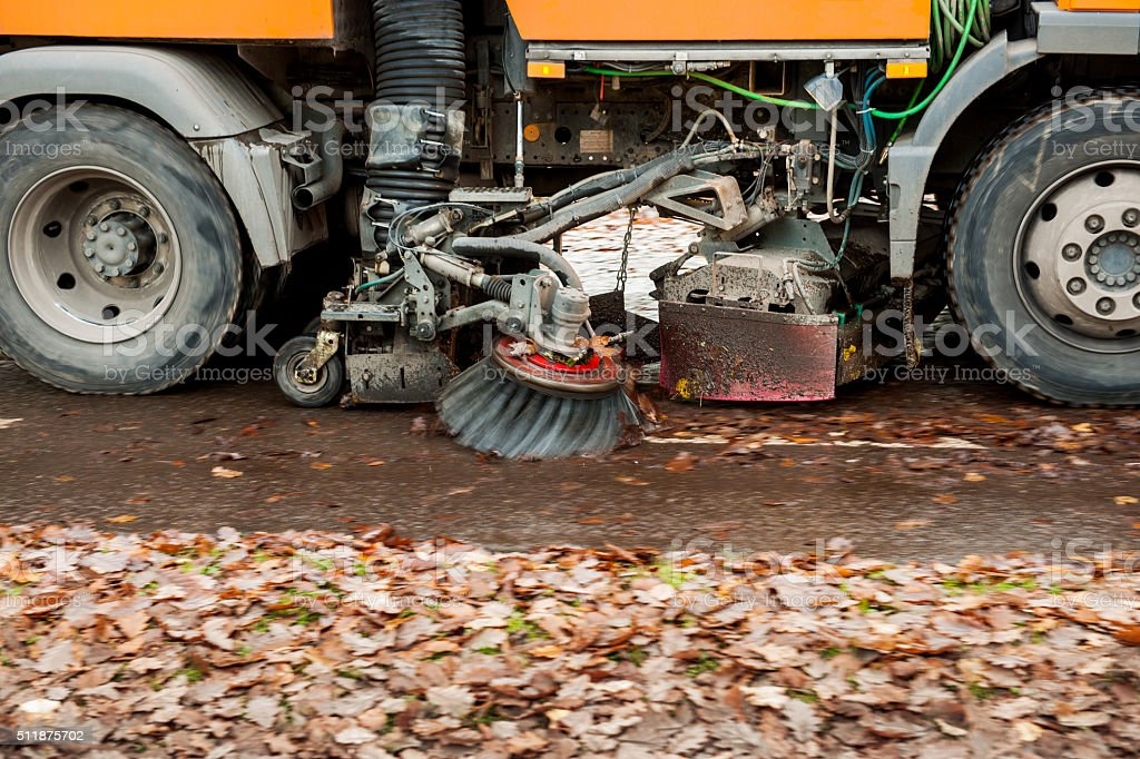 Orange street sweeper machine cleaning the street stock photo