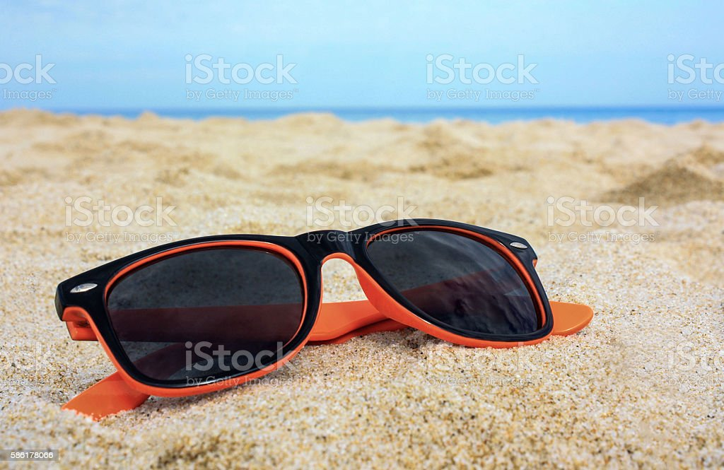 Orange sunglasses on the sand with sea on the background stock photo