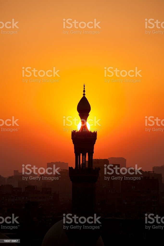 Orange sunset behind silhouette of mosque and town stock photo
