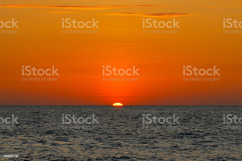 Orange Sunset in the ocean with calm water stock photo