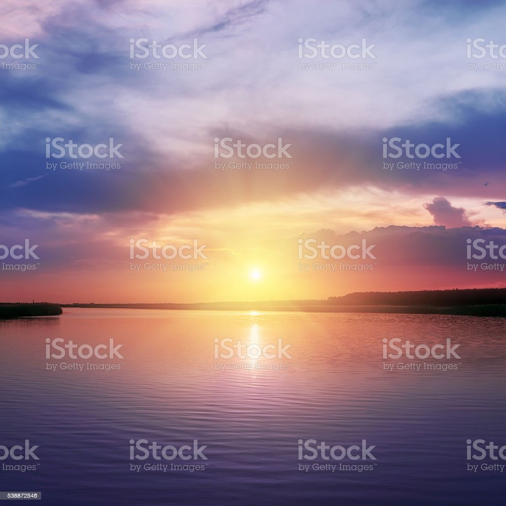 orange sunset over river in purple colors around stock photo