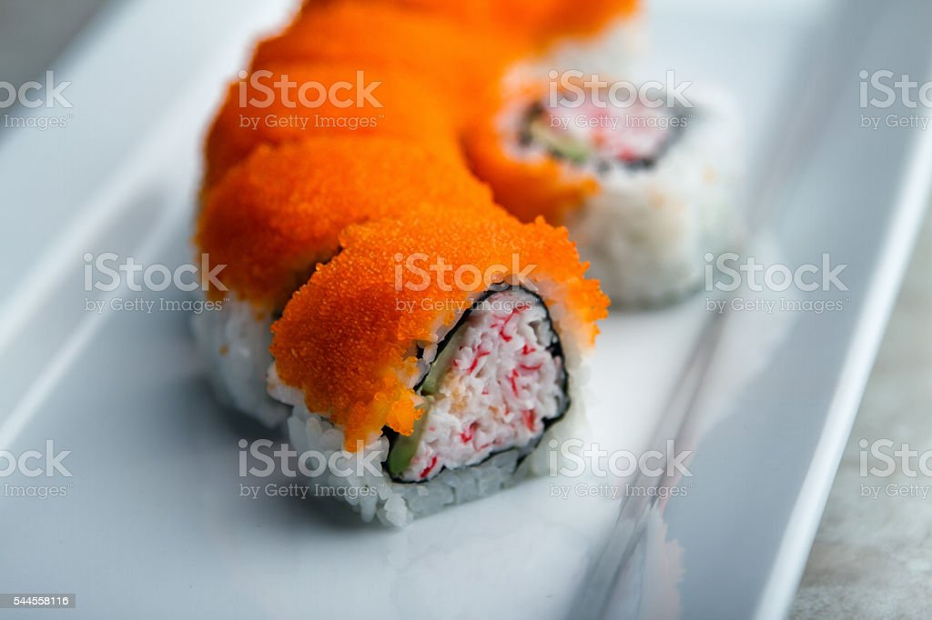 Orange Sushi Roll On A White Serving Dish stock photo