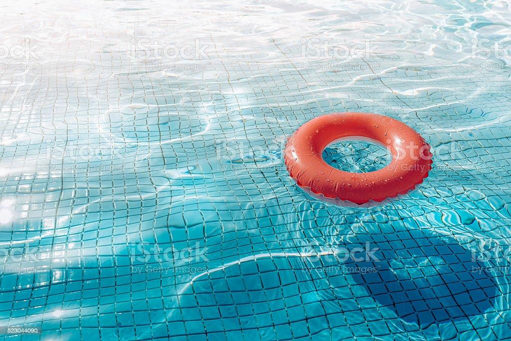 orange swim ring floating  in blue swimming pool stock photo