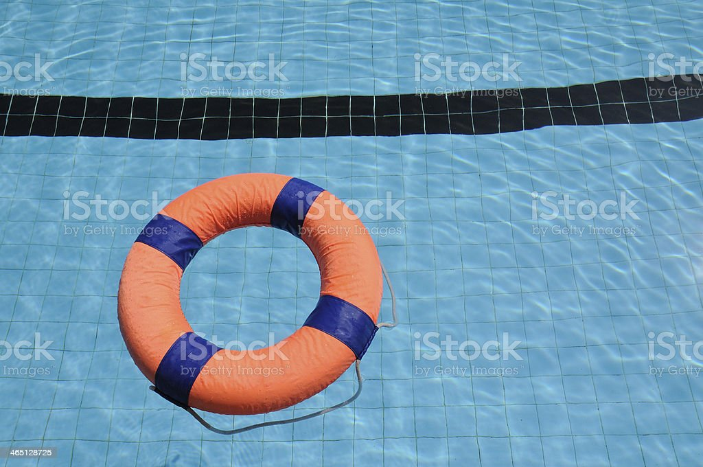 Orange swim ring with deep blue trim floating on water royalty-free stock photo