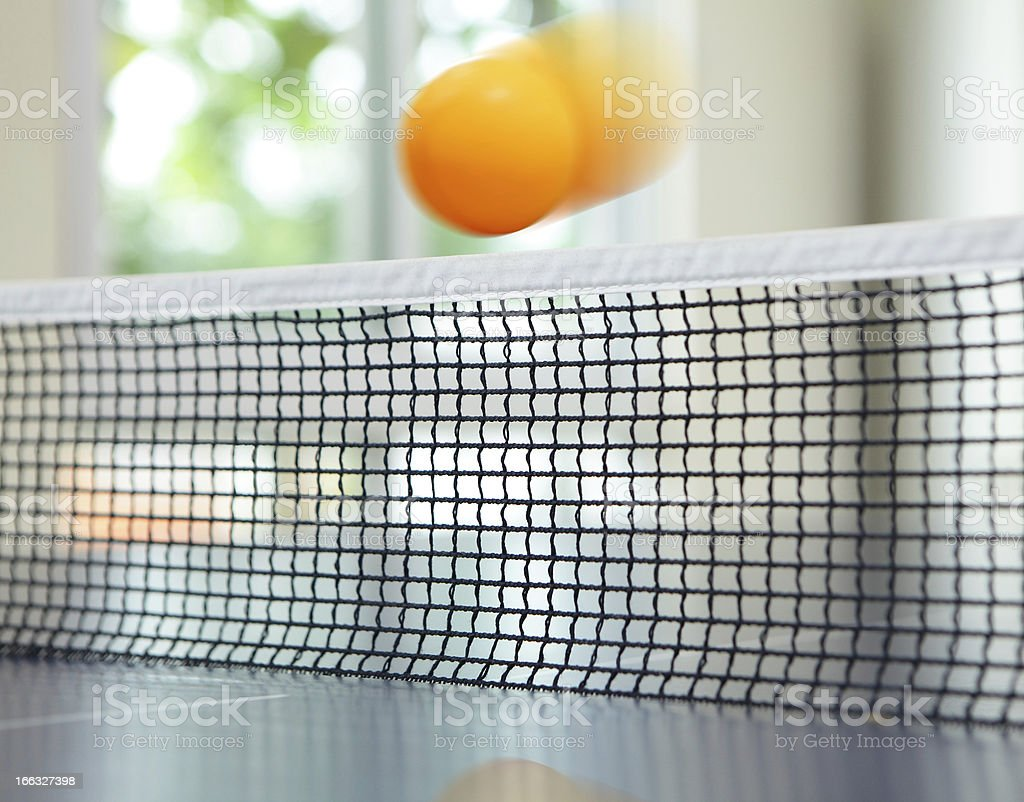 Orange table tennis ball moving over net royalty-free stock photo
