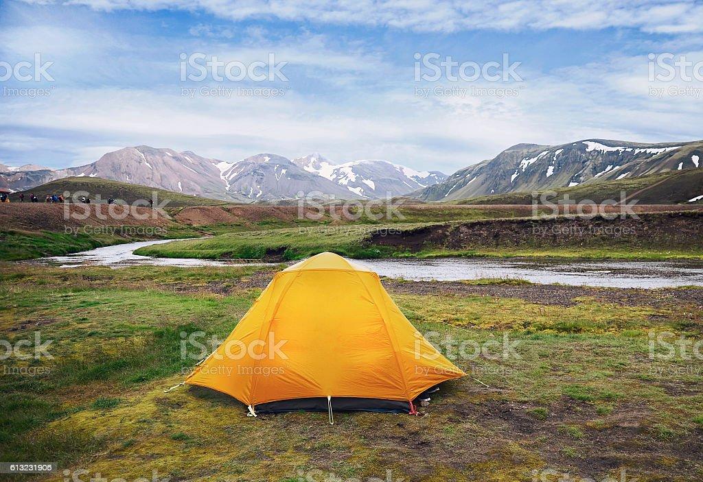 Orange tent on a river shore stock photo