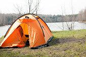 Orange tent on shore of lake.