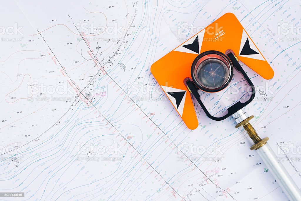 orange theodolite prism lies on a background geodetic maps stock photo