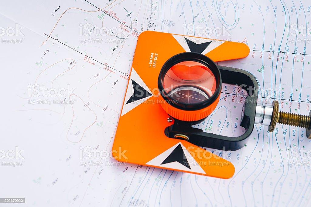 orange theodolite prism lies on a background geodetic maps stock photo