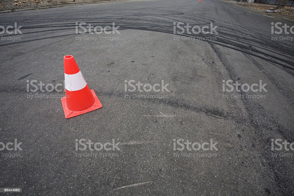 orange traffic cone and skid marks royalty-free stock photo