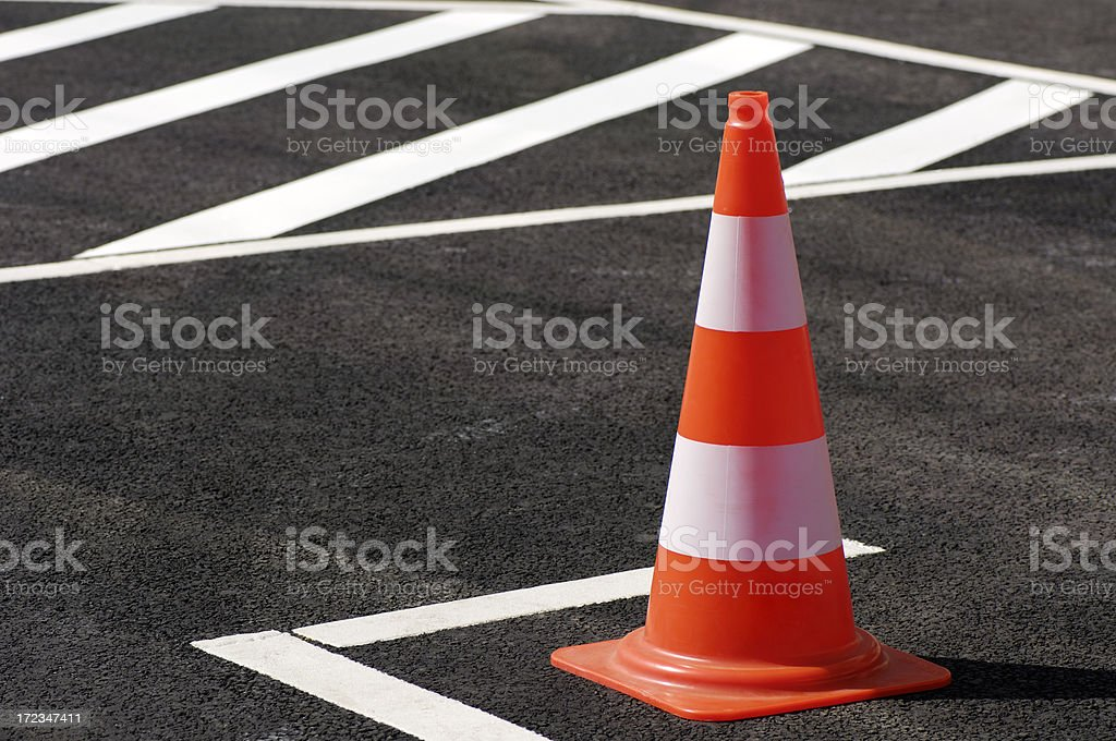 Orange traffic cone sitting on the black top pavement stock photo
