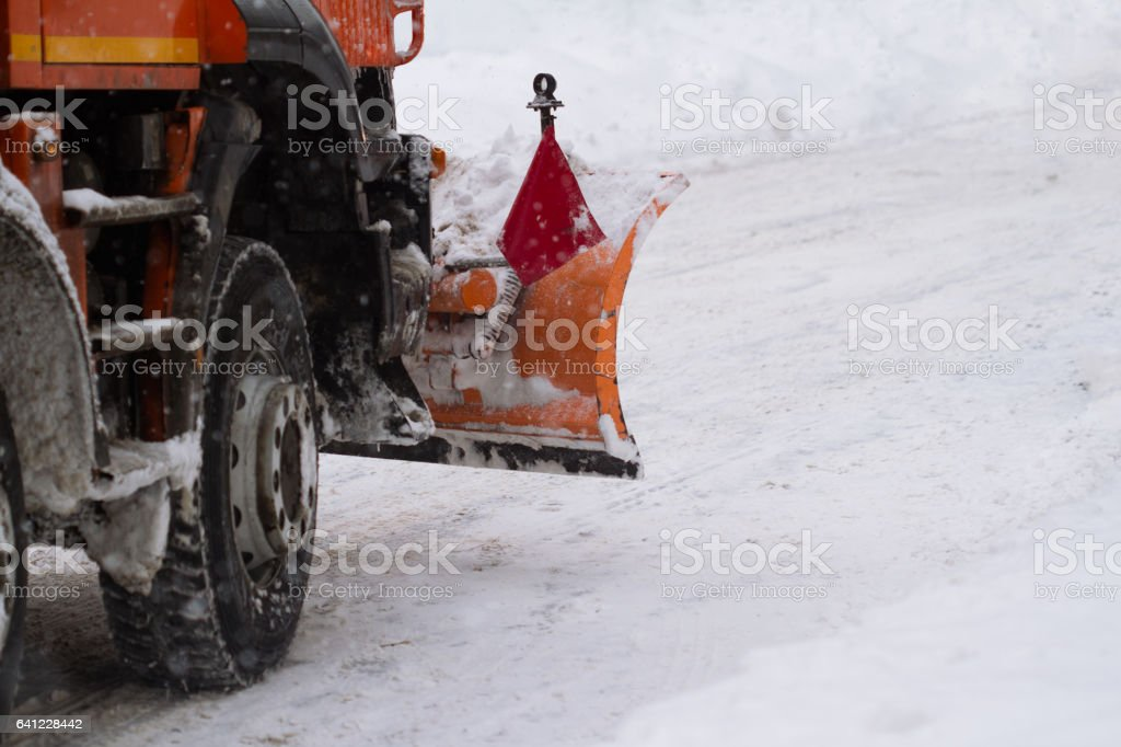 orange truck with plough driving down snow on city street stock photo
