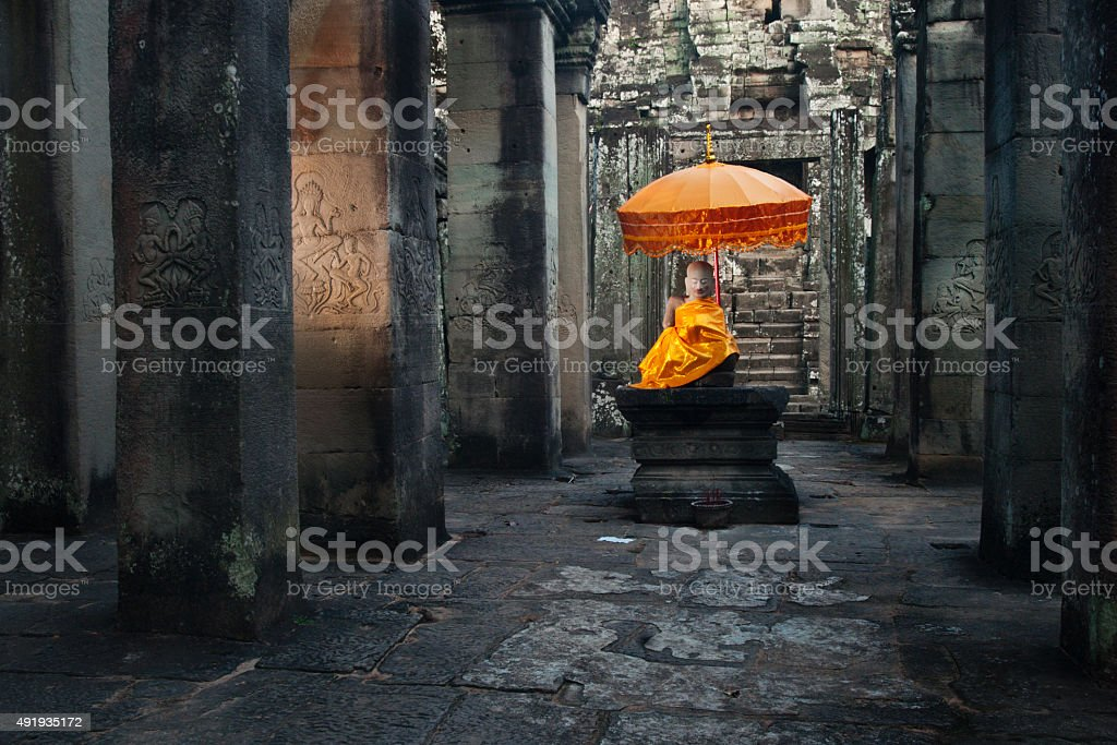Orange umbrella over Bhuddha at Angkor ruins stock photo