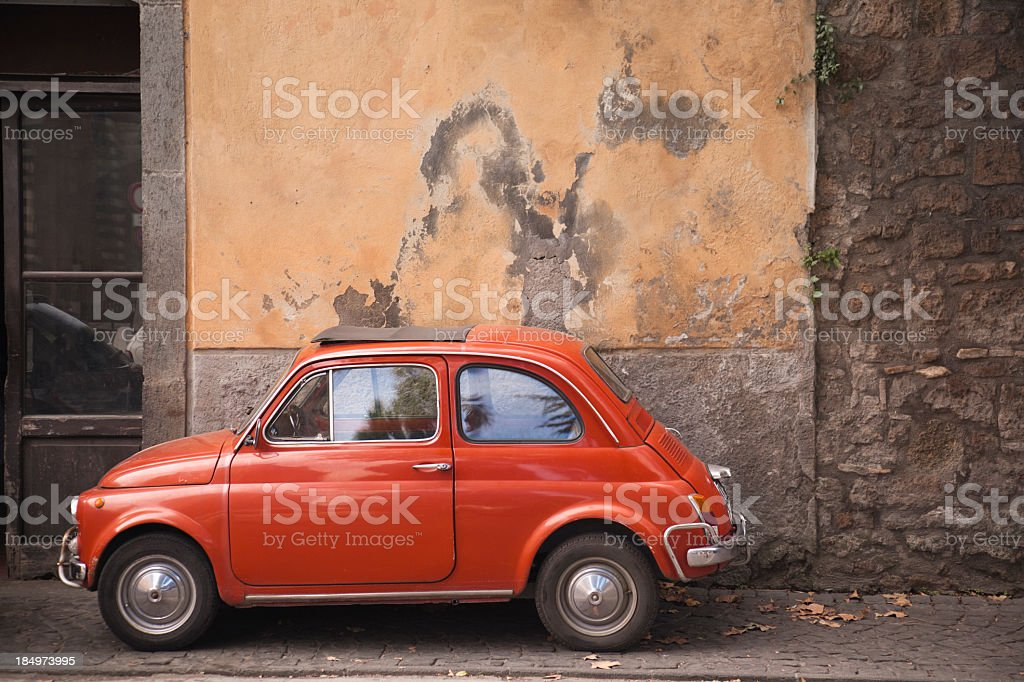 Orange vintage Italian car parked against a rusty wall stock photo