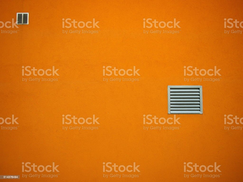 Orange wall with two small closed barred windows. stock photo