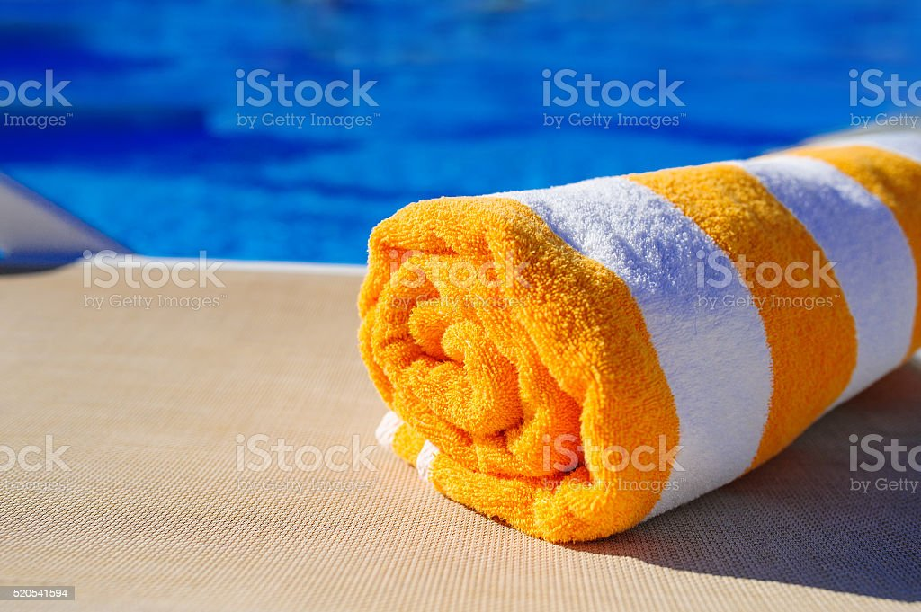 orange with white towel on a sun lounger background of stock photo
