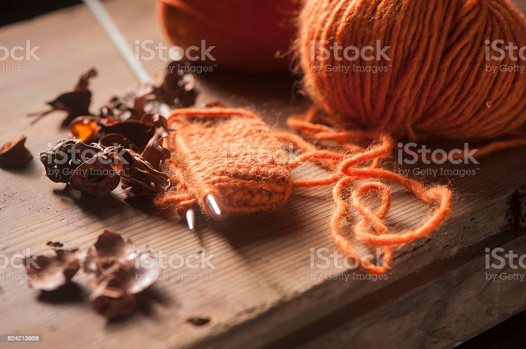 Orange woolen thread with knitted scarf stock photo