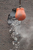 Orange wrecking ball smashing through brick on building