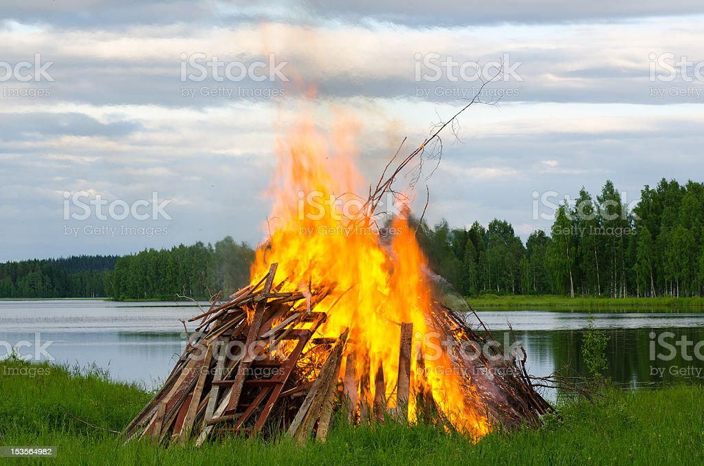 Orange-flames bonfire with sticks outdoors stock photo