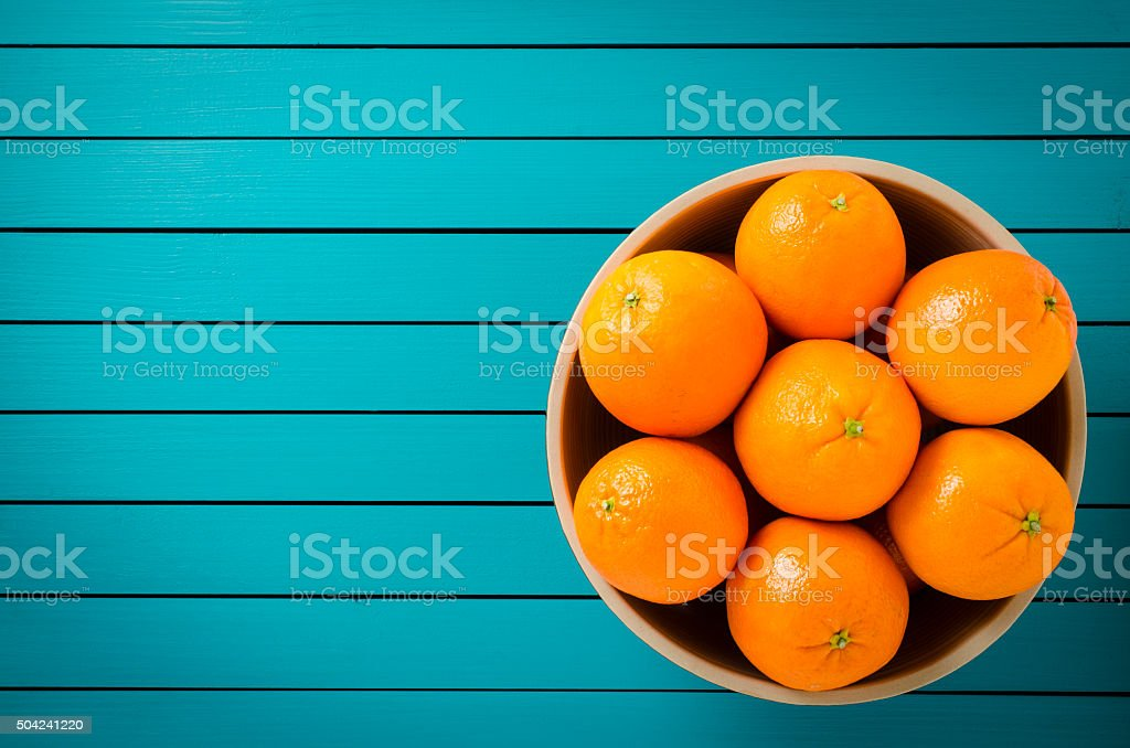 Oranges in bowl on wooden table stock photo