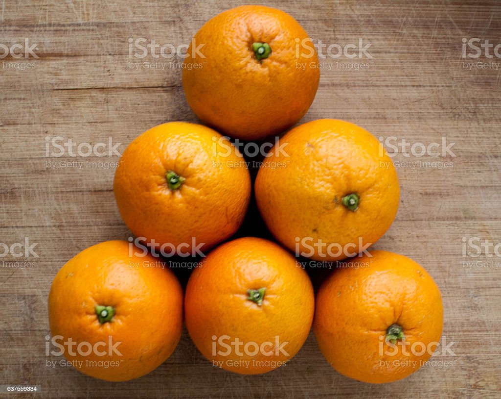 Oranges in piramide shape on wooden background stock photo