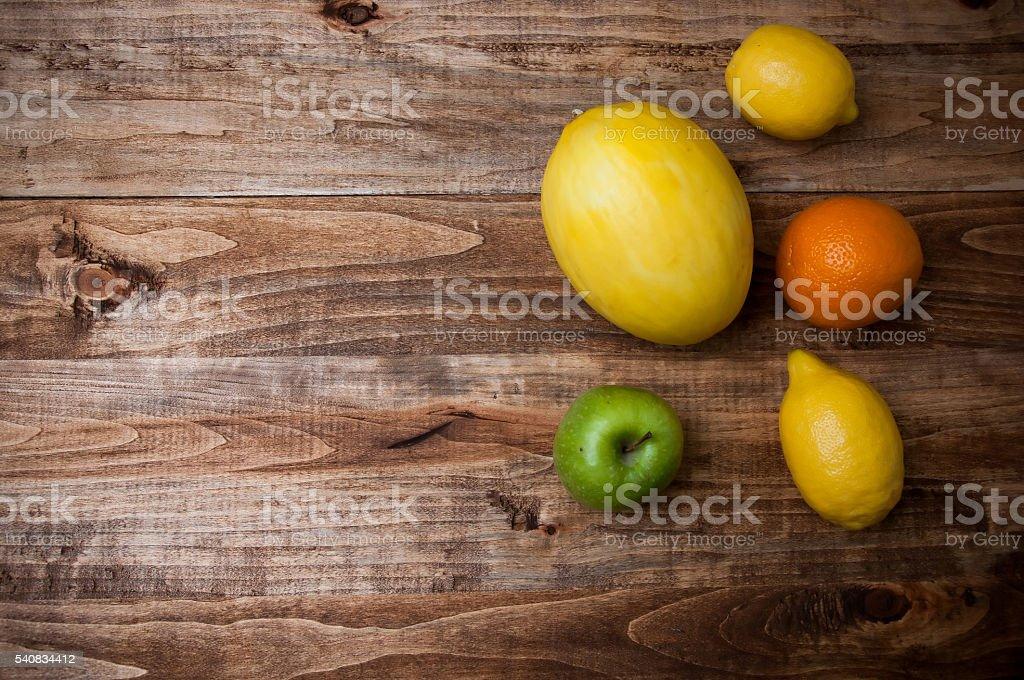 Oranges, lemon, apple and melon on wood stock photo
