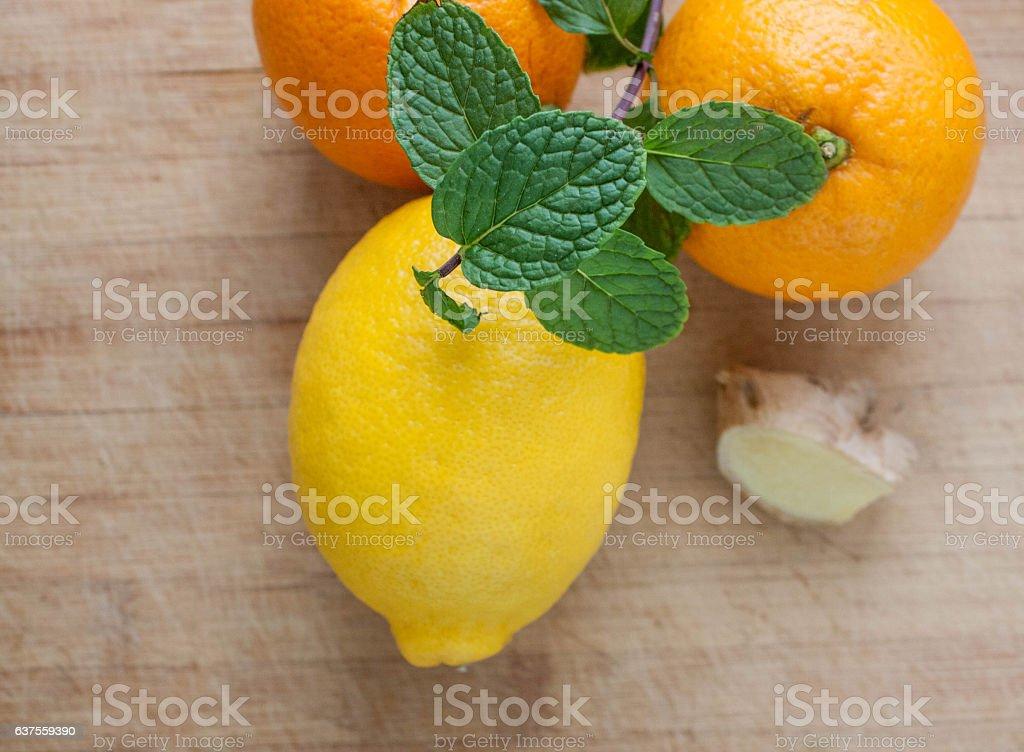 Oranges, lemon, mint and ginger on wooden background stock photo