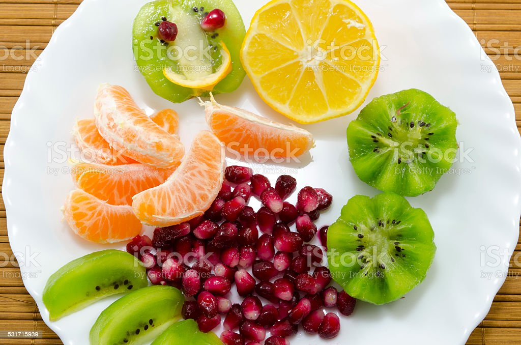Oranges, lemons, kiwis and pomegranate on a plate royalty-free stock photo