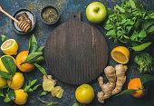 Oranges, mint, lemons, ginger, honey, apple, wooden board in center