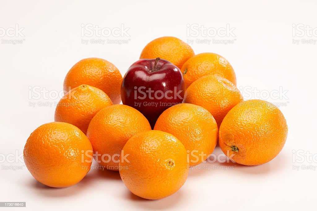 Oranges surround an apple stock photo