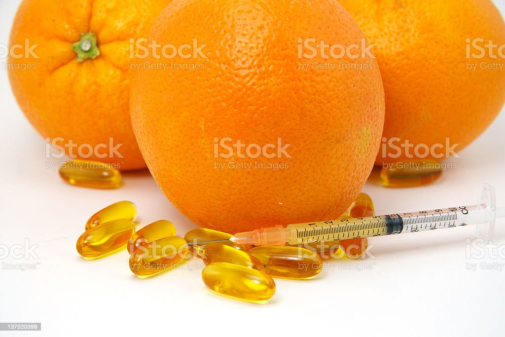 Oranges with gel capsule pills and syringe royalty-free stock photo