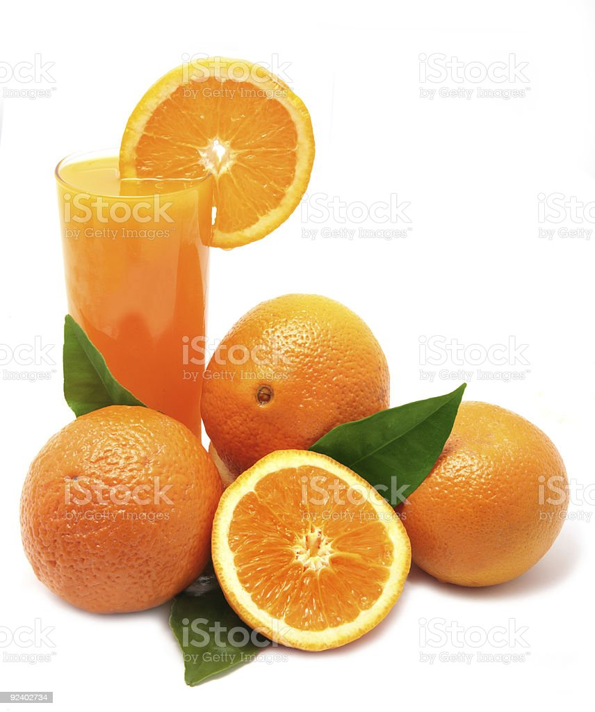 Oranges with green leaves and glass of juice royalty-free stock photo