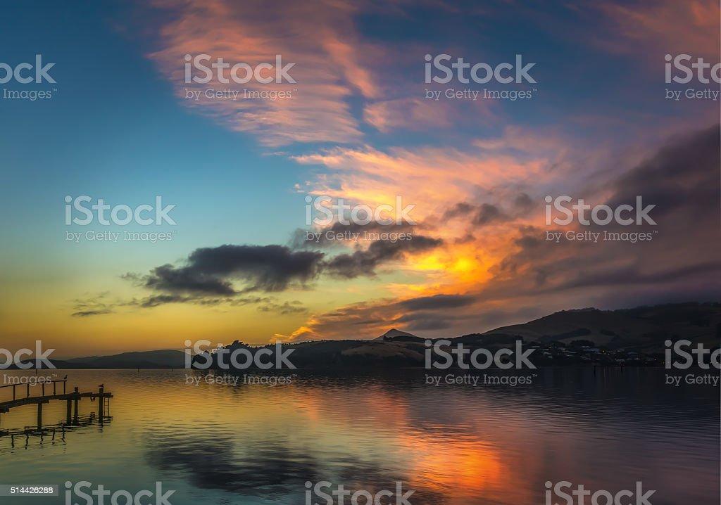 Orangey Red Sunrise With Clouds Over Otago Peninsula stock photo