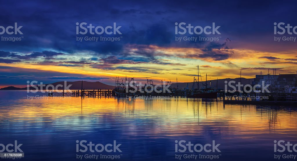 Orangey Sky Sunrise With Calm Waters At Port Chalmers stock photo