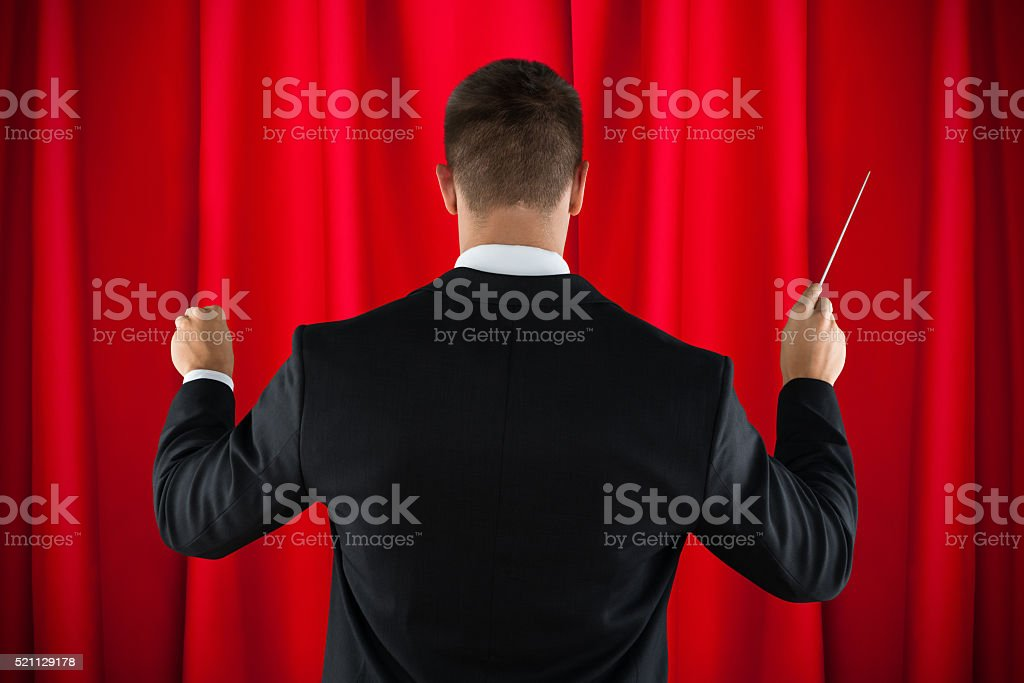 Orchestra Conductor Directing With His Baton stock photo