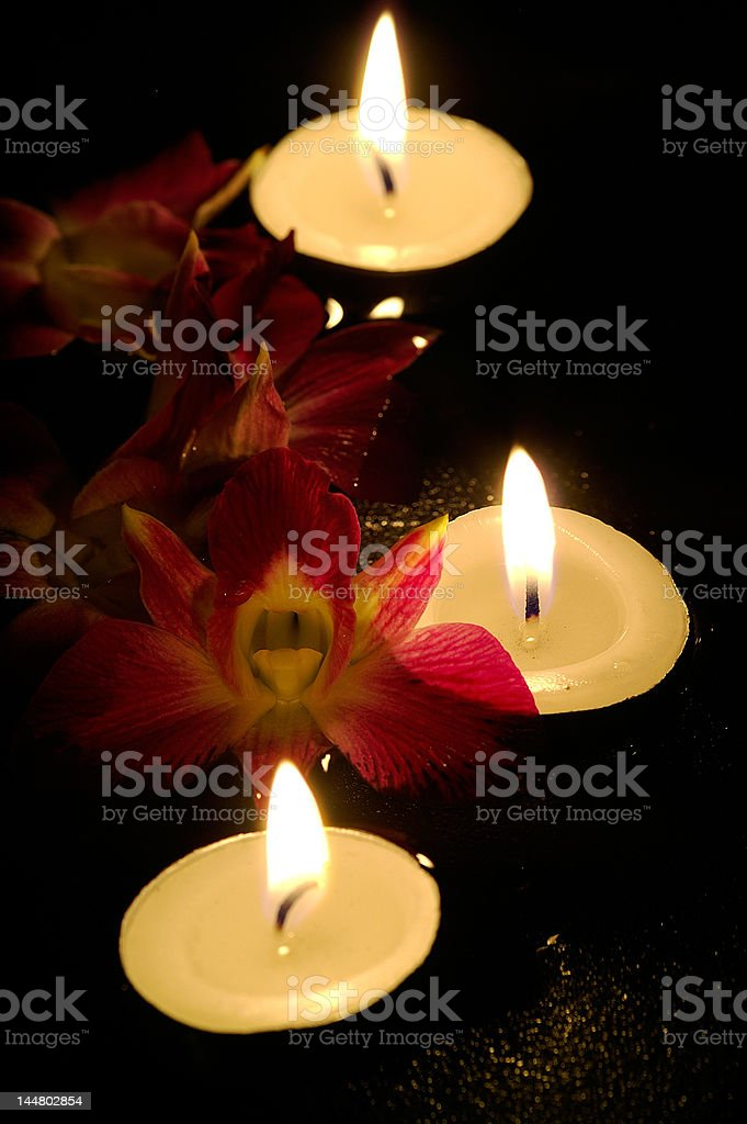 Orchids and tea lamps stock photo