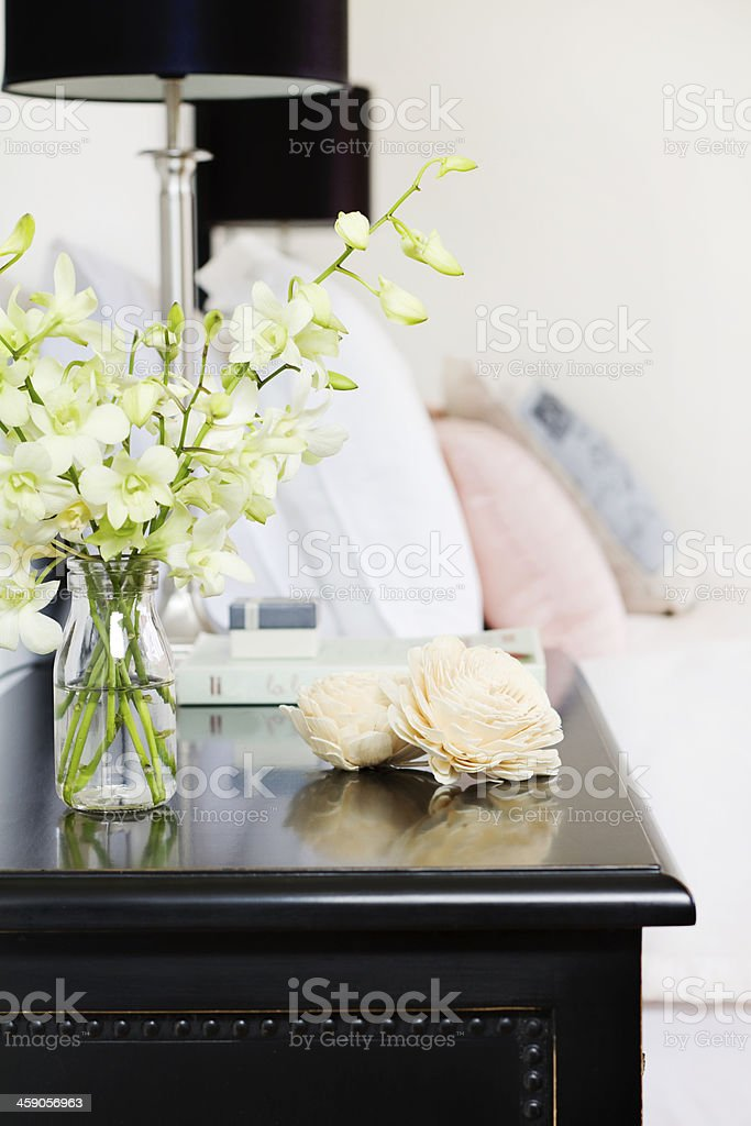 Orchids in vase on pretty bedside table vertical stock photo