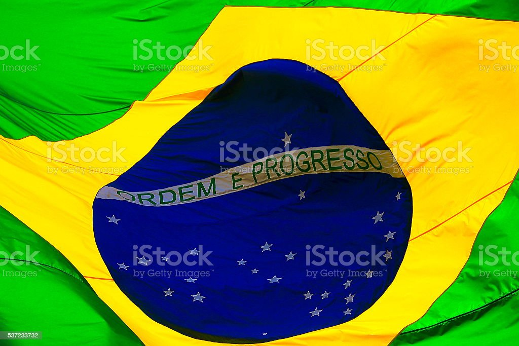 Ordem e Progresso: Brazillian Flag waving in the sky stock photo