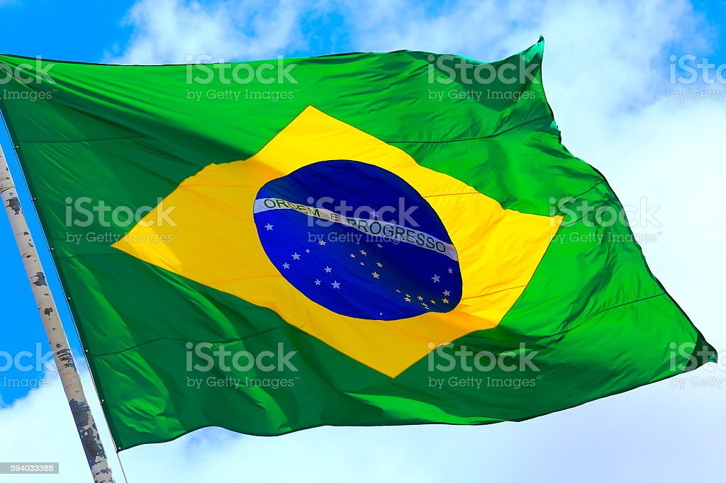 Ordem e Progresso: Colorful Brazillian Flag waving in the sky stock photo