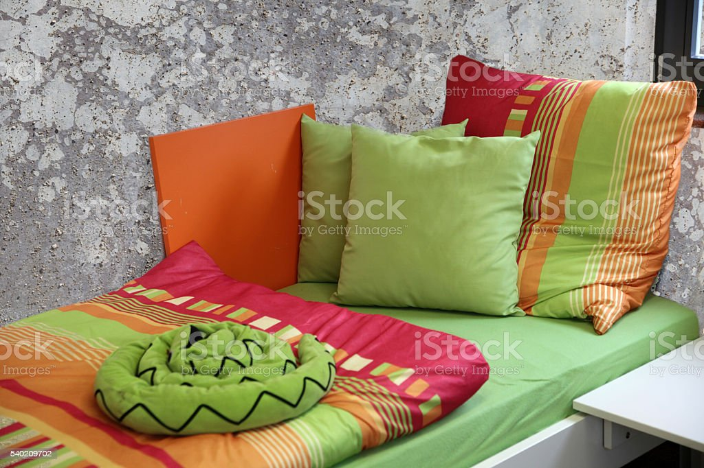 Orderly bed in front of dirty and unhygienic wall stock photo