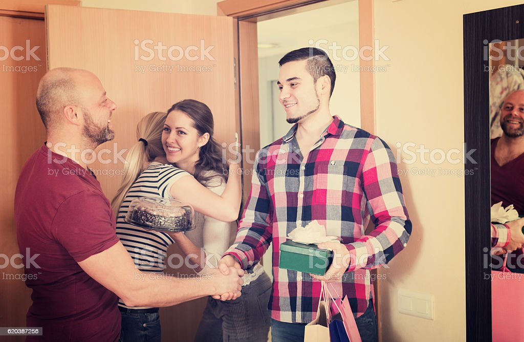Ordinary couple welcomes friends stock photo