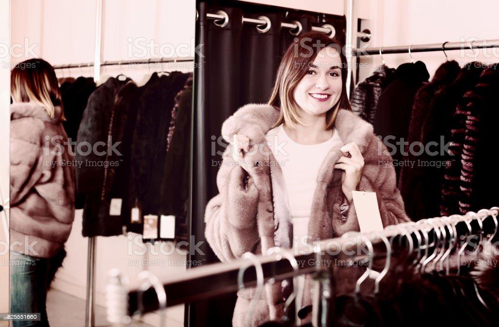 Ordinary girl deciding on the choice of fur coat stock photo