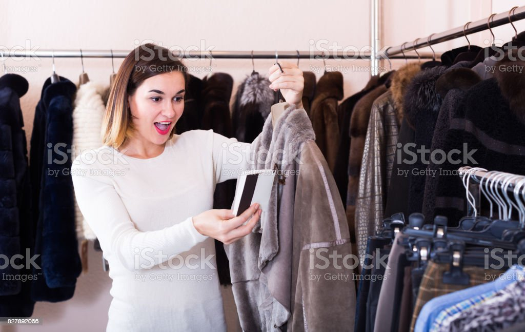 Ordinary girl deciding on warm sheepskin coat stock photo