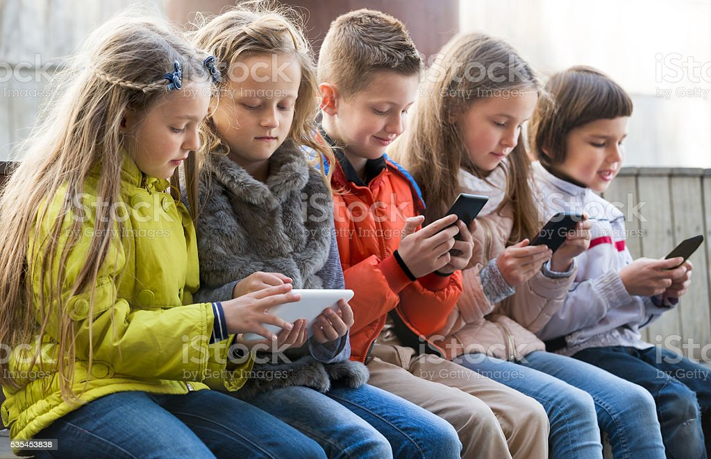 Ordinary kids sitting with mobile devices stock photo