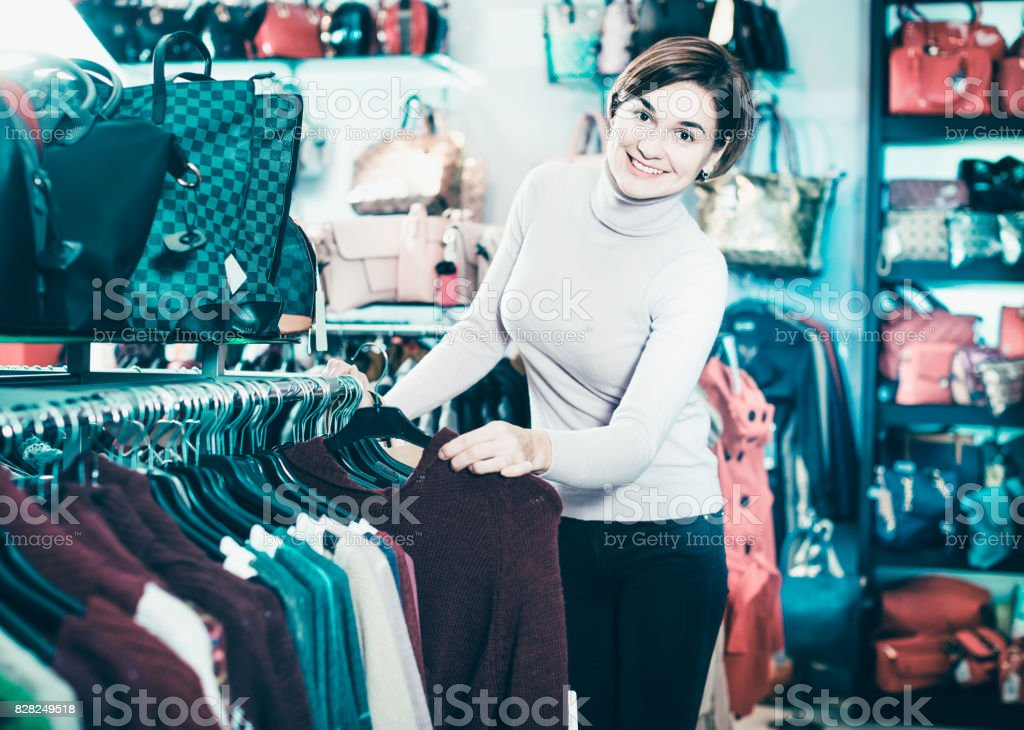 Ordinary woman choosing turtleneck sweater stock photo