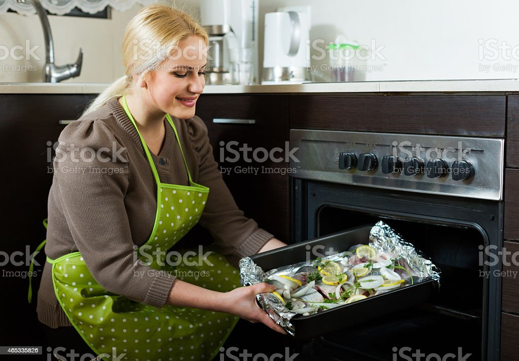 Ordinary woman cooking fish stock photo