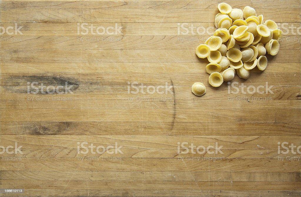Orecchiette Sitting on a Worn Cutting Board stock photo