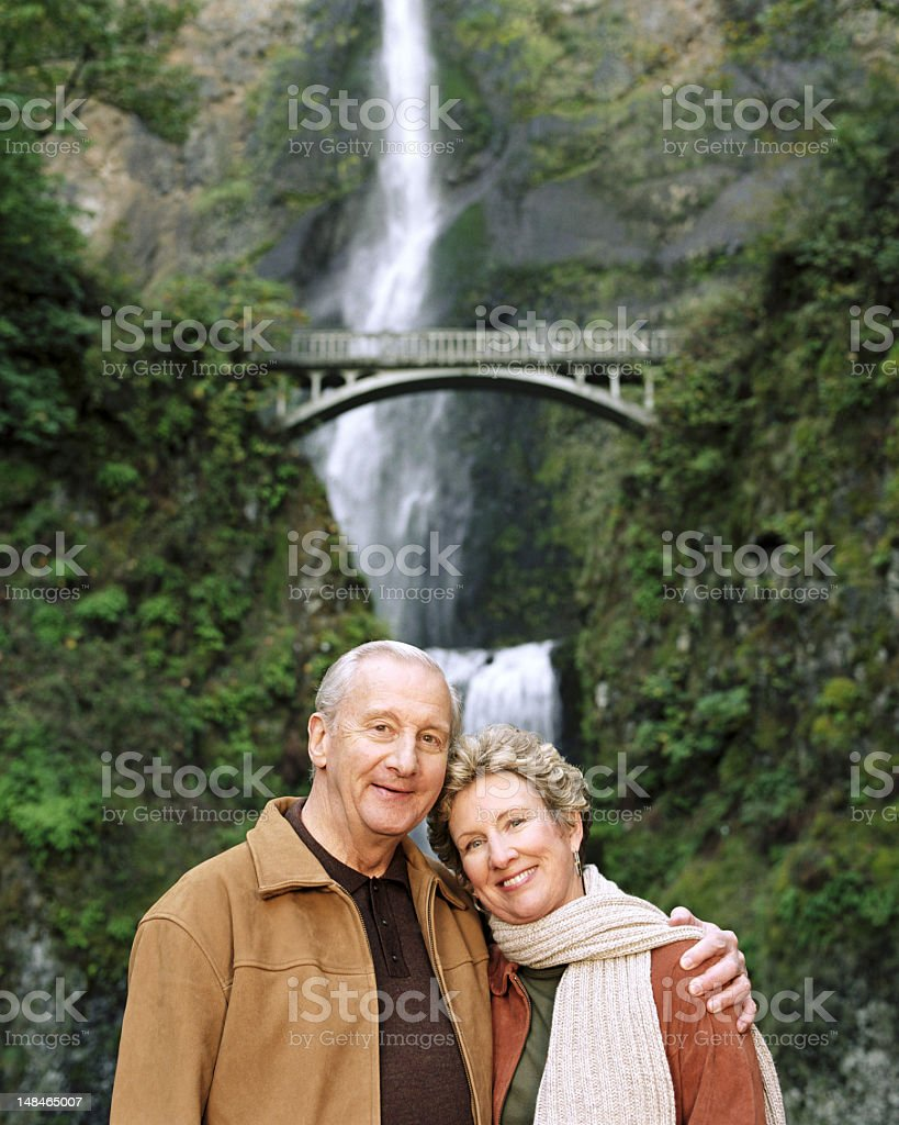 USA, Oregon, mature couple smiling, Multnomah Falls in backgroun stock photo